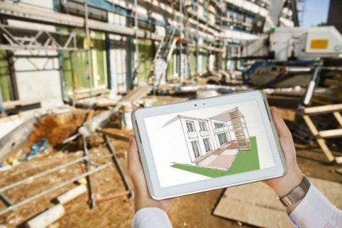 18 May 2013 --- Male hands holding a tablet PC with sketch of a house in front of a blurry construction site --- Image by © Mareen Fischinger/Corbis